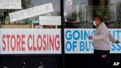 Čovjek prolazi pored izloga prodavnice u Ilinoisu, koja ne radi zbog COVID-19 (Foto: AP)