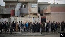 Warga Irak yang mengungsi dari Mosul barat antri untuk menerima pembagian makanan, Selasa (14/3).