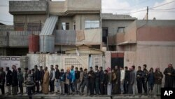 Iraqi civilians line up to receive food supplies in a neighborhood recently liberated by Iraqi security forces in western Mosul, March 14, 2017.