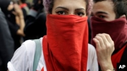 A demonstrator with her face covered marches during a protest on the route of the Olympic torch against the money spent on the Rio's 2016 Summer Olympics, in Niteroi, Brazil, Tuesday, Aug. 2, 2016.