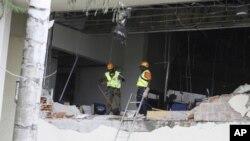 星期五﹐有關人員在阿布賈的聯合國辦公樓被炸後進行搜救工作