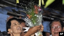 Burma's pro-democracy leader Aung San Suu Kyi smiles after she received flowers from her supporters as she stands at the gate of her home in Rangoon, 13 Nov 2010