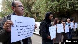"""Warga Mesir melakukan aksi unjuk rasa di depan Kedutaan Italia di Kairo atas tewasnya Giulio Regeni dengan membawa tulisan: """"Gulio, seorang di antara kami dan tewas dibunuh seperti kami"""", Sabtu (6/2)."""
