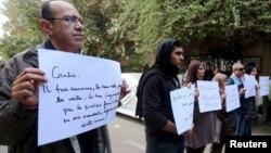 """Các nhà hoạt động giơ những tấm bảng có dòng chữ """"Giulio, một trong số chúng ta và đã bị giết như chúng ta"""" trong buổi lễ tưởng niệm Giulio Regeni bên ngoài Đại sứ quán Ý tại Cairo, Ai Cập, ngày 6/2/2016."""
