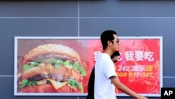 Two Chinese men walk past a billboard advertising US fast-food giant McDonald's, in Yichang, central China's Hubei province (Jul 2010 file photo)