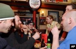 Para mahasiswa menikmati bir di sebuah pub di Cambridge, Massachusetts, 24 Maret 2002. (Foto: AP)
