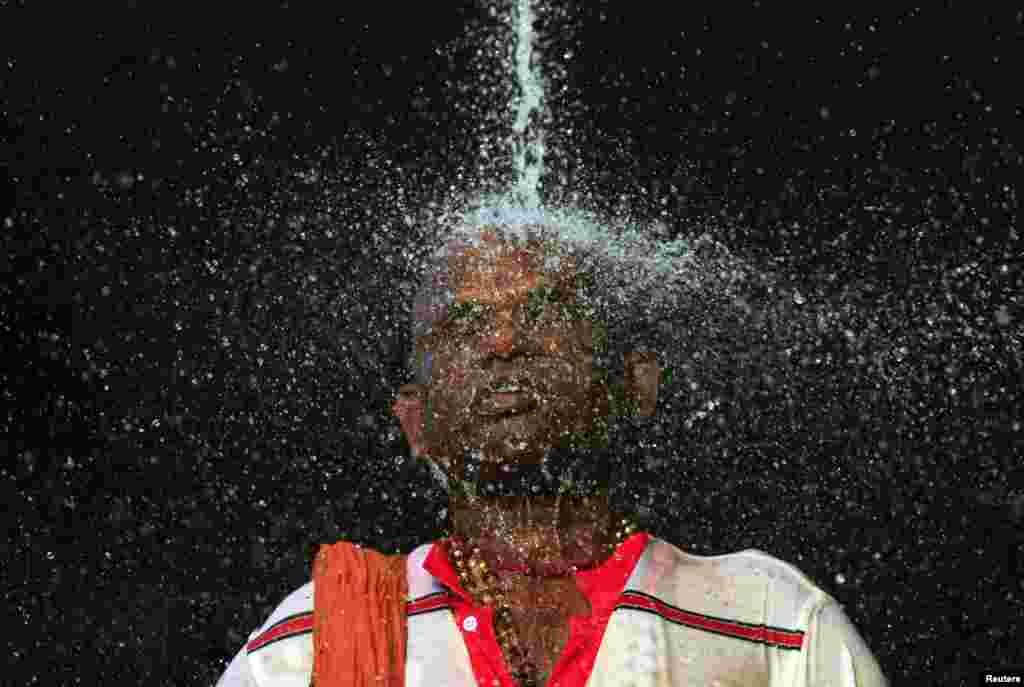 A Hindu devotee takes a ritual shower before he starts his pilgrimage to the sacred Batu Caves Temple during Thaipusam festival outside Kuala Lumpur, Malaysia. Thousands of Hindus participate in the annual thanksgiving festival in which devotees subject themselves to painful rituals in a demonstration of faith and penance held in honor of Lord Subramaniam.