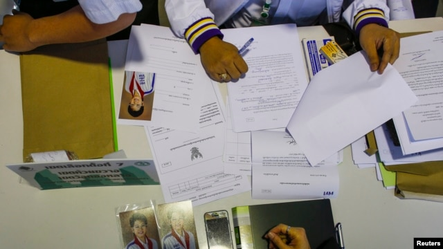 Photographs of Poowanida Kunpalin from the ruling Puea Thai Party are seen as her documents are inspected during a registration of election candidates near the Government complex in Bangkok, Thailand, Dec. 28, 2013.