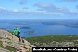 Mikah Meyer sits on Cadillac Mountain, the highest point along the U.S. east coast.