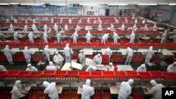 双汇集团在中国河南省漯河的一家猪肉加工厂生产线上的员工。(资料照)