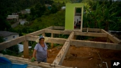 FILE - Alma Morales Rosario is pictured between the beams of her home being rebuilt after it was destroyed by Hurricane Maria one year ago in the San Lorenzo neighborhood of Morovis, Puerto Rico, Sept. 8, 2018.