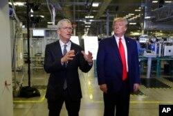 Apple CEO'su Tim Cook, Kasım 2019'da Apple fabrikası ziyareti sırasında Başkan Trump'a eşlik ederken