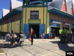Customers sit outside the Caribbean Marketplace in Little Haiti, Miami, Florida. (Photo: S. Lemaire / VOA)
