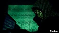 Un homme portant une capuche utilise un ordinateur portable dont le code cybernétique est projeté sur lui. Image illustrée prise le 13 mai 2017.