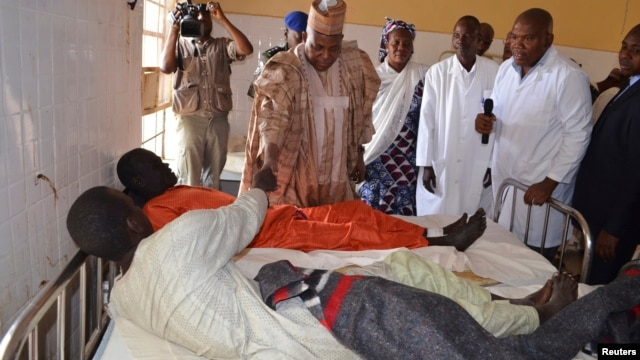 Borno State Governor Kashim Shettima visits injured victims receiving treatment at a hospital following an attack in Kawuri on January 28, 2014.
