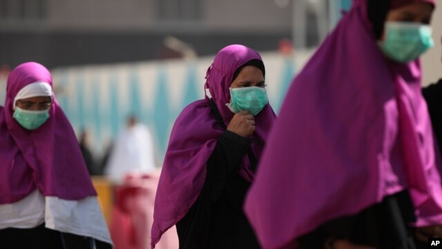Muslim pilgrims wears surgical masks to help prevent infection from a respiratory virus known as the Middle East Respiratory Syndrome (MERS) in the holy city of Mecca, Saudi Arabia, May 13, 2014.