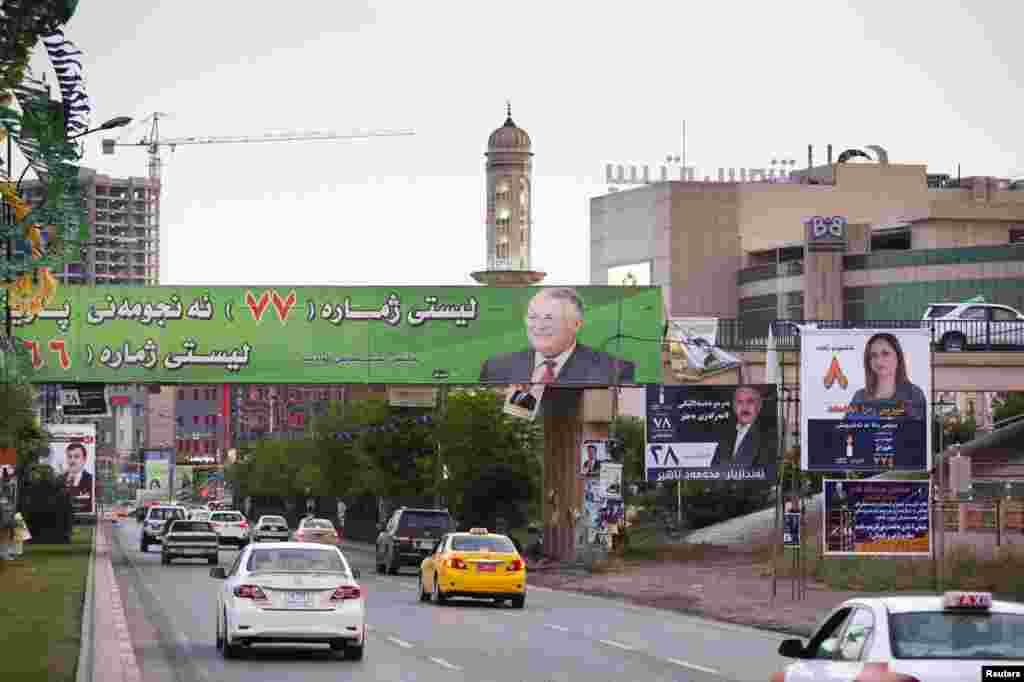 Vehicles drive under a campaign poster of Iraq's President Jalal Talabani (in green) of the Patriotic Union of Kurdistan (PUK) before the country's parliamentary elections in Sulaimaniya April 28, 2014. Picture taken April 28, 2014. To match IRAQ-E