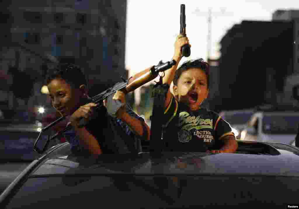 Palestinian children hold guns in Gaza City as they celebrate with others what they said was a victory over Israel, following a ceasefire. Israel has accepted an Egyptian proposal for a Gaza ceasefire, a senior Israeli official said.