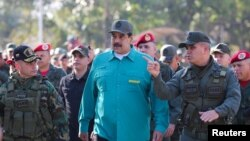 Venezuelan President Nicolas Maduro speaks with senior military officials during a military exercise in Valencia, Venezuela, Jan. 27, 2019.