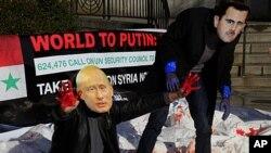 Nhóm cổ võ cho nhân quyền Avaaz và các nhà hoạt động, dùng máu giả và đeo mặt nạ hình nhà lãnh đạo Syria al-Assad và Tổng thống Nga Vladimir Putin, biểu tình bên ngoài trụ sở Liên hiệp quốc ở New York