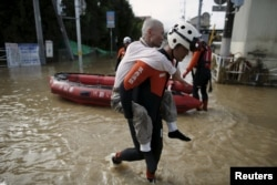 An elderly man is rescued by a firefighter at a residential area flooded by the Kinugawa river, caused by typhoon Etau in Joso, Ibaraki prefecture, Japan, Sept. 11, 2015.