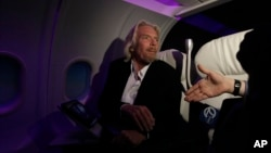 FILE - Virgin Group Founder Richard Branson greets a reporter as he sits in a Virgin America aircraft replica at an opening for a new cabin trainer facility at Virgin America corporate headquarters in Burlingame, California, Oct. 18, 2011.