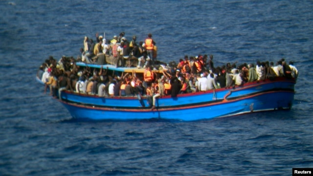 Migrants sit in their boat during a rescue operation by Italian navy ship Grecale (not pictured) off the coast of Sicily, in this handout picture by the Italian Marina Militare, June 29, 2014.
