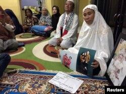 Susmawati, guru sekolah dasar di kediamannya di Pangkal Pinang, menunjukkan foto putrinya, Wita Seriani dan keluarganya, yang menjadi korban kecelakaan pesawat Lion Air JT610, 31 Oktober 2018.(Foto: Reuters)