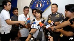 "Police Lt. Gen. Thitiraj Nhongharnpitak, second right, watches Noppawan ""Ploy"" Bunluesilp, center, wife of British journalist Andrew McGregor Marshall, address the media as she prepares to leave a Bangkok police station on July 22, 2016."