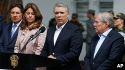 Colombia's President Ivan Duque gives a statement inside the General Santander police academy after a bomb exploded on the campus in Bogota, Jan. 17, 2019. At right is Defense Minister Guillermo Botero and at left is Vice President Martha Lucia Ramirez.