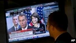El especialista Frank Masiello escucha las declaraciones del John Boehner en la televisión mientras trabaja en la Bolsa de Valores de Nueva York.