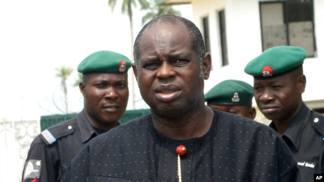 Bayelsa State Governor Diepreye Alamieyeseigha stands outside his house guarded by policemen in Yenagoa, Nigeria, in this photo dated November 27, 2005.