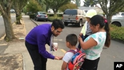 Oscar Belanger, assistant principal of Nellie Muir Elementary School, in Woodburn, Oregon, where 82 percent of students are Latino, slaps five with a student arriving for the first day of class on Tuesday, Sept. 5, 2017.