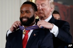 President Donald Trump presents Capitol Hill police Officer David Bailey the Medal of Valor during a ceremony in the East Room of the White House in Washington, July 27, 2017.