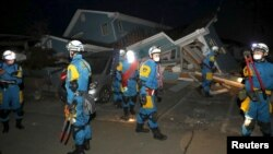 Police officers check a collapsed house after an earthquake in Mashiki town, Kumamoto prefecture, southern Japan, April 16, 2016.