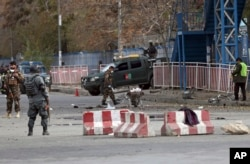 FILE - Security forces inspect the site of a deadly blast near a demonstration by hundreds of minority Shi'ites, in the center of Kabul, Afghanistan, Nov. 12, 2018. Afghan officials confirmed several people were killed in the explosion about 500 meters (yards) from where people gathered to denounce Taliban attacks in Jaghuri and Malistan districts of eastern Ghazni province.
