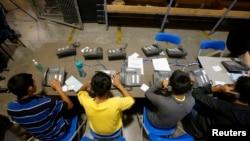 Niños aprehendidos en Arizona tratan de hacer llamadas telefónicas para comunicarse con sus familiares.
