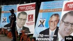 Petugas keamanan sedang berjaga di depan papan kampanye calon presiden Otto Perez Molina dan Manuel Baldizon di Guatemala (5/11).