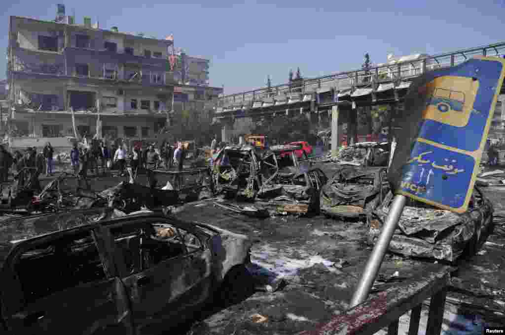 People walk near debris and damaged vehicles after an explosion in central Damascus February 21, 2013. Residents said that the big explosion shook the central Damascus district of al-Mazraa.