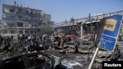 Người dân đi qua những mảnh vụn của các phương tiện bị phá hủy do vụ nổ xảy ra ở trung tâm Damascus, 21/2/2013.