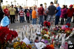 People pray at a makeshift memorial to honor the victims of Wednesday's shooting rampage, Dec. 5, 2015, in San Bernardino, Calif.
