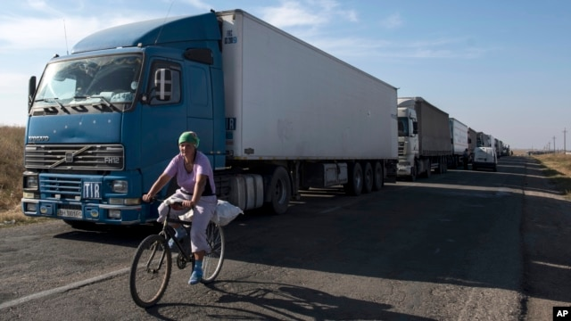 FILE - A local resident rides her bicycle as trucks are parked on a blocked road heading toward Crimea, in the village of Chaplinka, Ukraine, on Sunday, Sept. 20, 2015.
