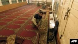 Một người đang dọn dẹp kính của đền thờ bị vỡ do vụ nổ