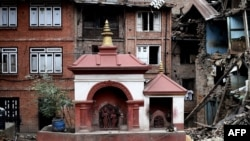 FILE - A small temple structure is seen undamaged amidst rubble of damaged buildings at the heritage town of Bhaktapur on April 29, 2015.