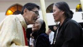 Linh mục Matthew Vũ Khởi Phụng ban phước cho mẹ và chị của ông Ðoàn Văn Vươn.