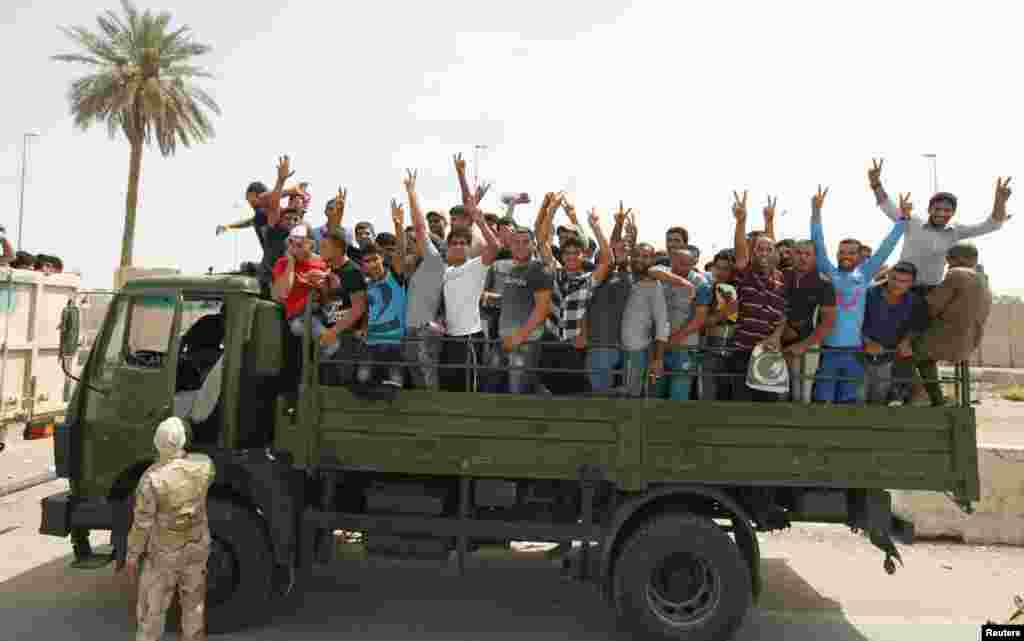 Volunteers who have joined the Iraqi Army to fight against the predominantly Sunni militants gesture from an army truck, Baghdad, June 13, 2014.