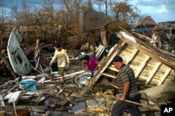 Affected by Hurricane Irma people seek to save their belongings in their destroyed house in Isabela de Sagua, Cuba, Sept. 11, 2017.