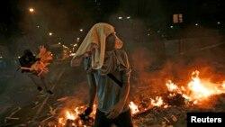 2014年2月20日在委内瑞拉的加拉加斯市反对派支持人士走过燃烧的挡墙。