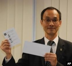 香港大學民意研究計劃總監鍾庭耀展示民間全民投票的選票及投票時使用的信封