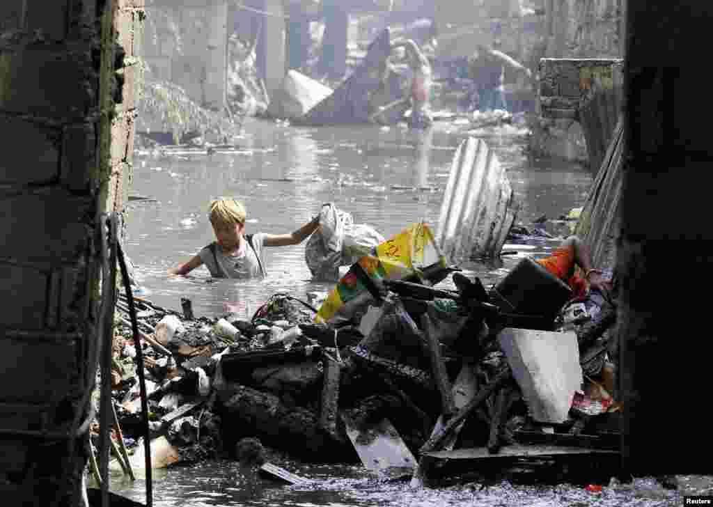 필리핀 마닐라 도심의 빈민가에서 한 소년이 쓰레기가 쌓인 하수에서 재활용품을 수집하고 있다.